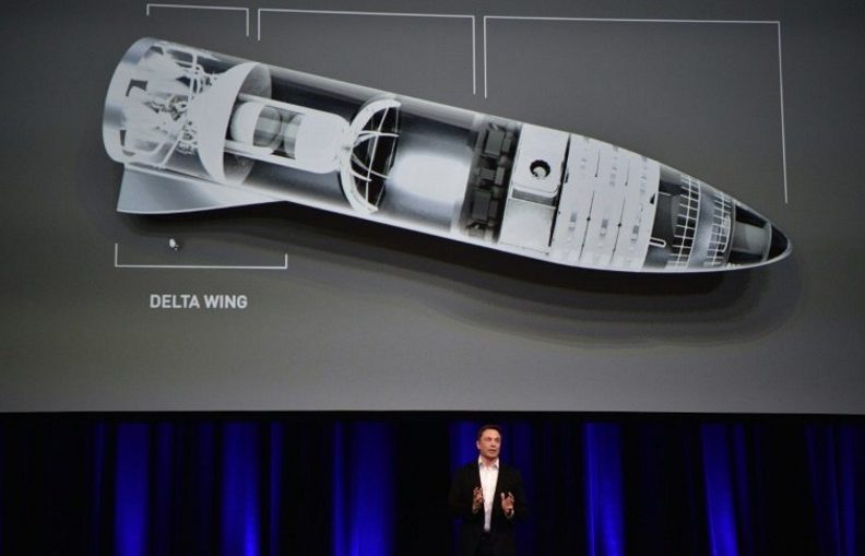 """Billionaire entrepreneur and founder of SpaceX Elon Musk, pictured in September 2017 speaking below a computer generated illustration of his new rocket, says he wants to enable space travel for """"everyday people"""""""